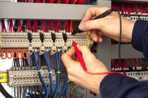 Electrician testing industrial panel